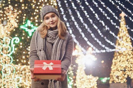 Girl holding gift box on winter festival. Celebrate New Year EVE. Against a background the Christmas lights. Фото со стока - 137761625