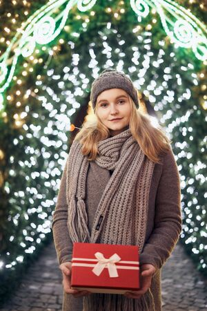 Girl holding gift box on winter festival. Celebrate New Year EVE. Against a background the Christmas lights. Фото со стока - 137761626