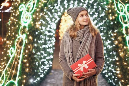 Girl holding gift box on winter festival. Celebrate New Year EVE. Against a background the Christmas lights. Фото со стока - 137761627