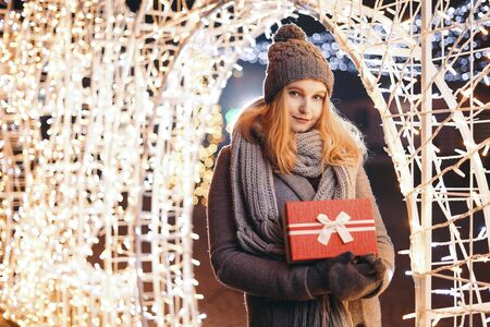 Girl holding gift box on winter festival. Celebrate New Year EVE. Against a background the Christmas lights. Фото со стока - 137761630