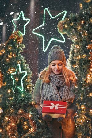 Girl holding gift box on winter festival. Celebrate New Year EVE. Against a background the Christmas lights. Фото со стока - 137761677