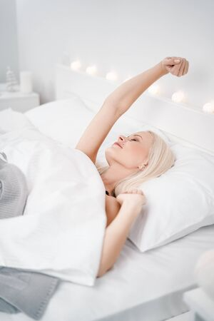 Happy girl waking up stretching arms on the bed in the morning.