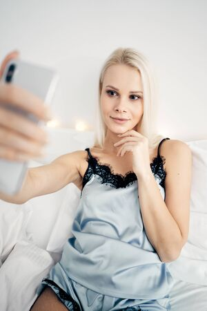 Sharing photos. Top view of attractive young woman taking selfie and smiling while sitting on bed at home 版權商用圖片