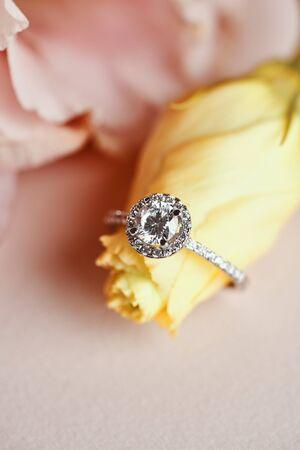 Diamantring und rosa Blumenhintergrund. Nahaufnahme von einem eleganten Diamant-Verlobungsring.