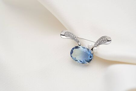 Silver brooch shaped like a hare with blue iridescent crystal, isolated on white background. Women Accessories