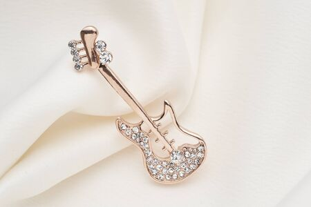 Silver brooch shaped like a guitar, with small diamonds, isolated on white background. Women Accessories
