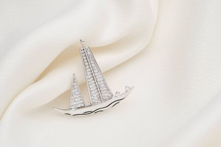 Silver brooch shaped like a ship, with small diamonds, isolated on white background. Women Accessories