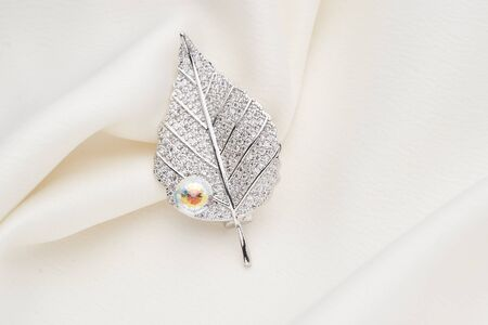 Silver brooch shaped like a leaf, with small diamonds, isolated on white background. Women Accessories