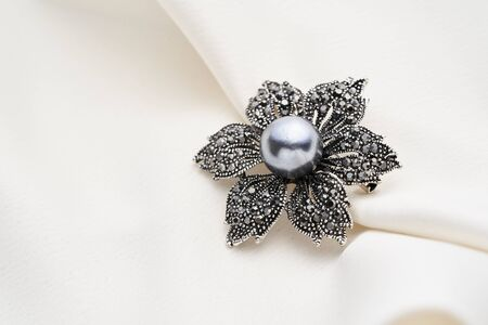 Silver brooch shaped like a flower with small diamonds and black pearl, isolated on white background. Women Accessories