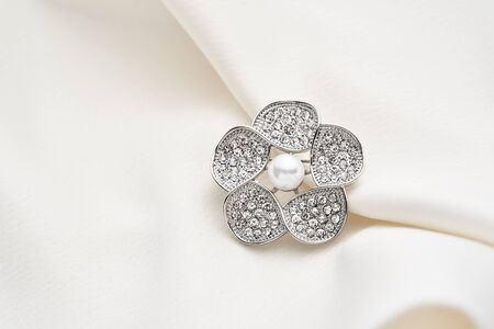 Silver brooch shaped like a flower with small diamonds and white pearl, isolated on white background. Women Accessories