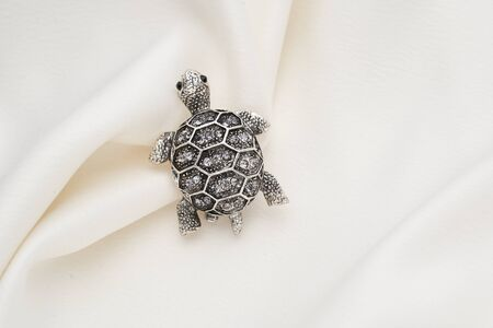 Silver brooch shaped like a turtle with small diamonds, isolated on white background. Women Accessories