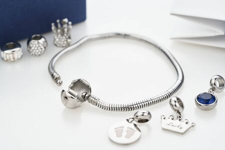 Beautiful stylish bracelet with silver charm beads with gems, isolated on white background. Assorted metal charm pendants for necklace or bracelet. Women accessories. Stock Photo