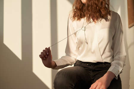 Charming brunette woman with curly hairstyle and perfect clear skin wearing white blouse and stylish long necklace. Necklace with white crystals and diamonds. Unusual and elegant pendant