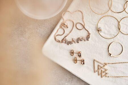 Luxury jewelry set of long earrings, pendant, butterfly bracelet, ring, stud earrings on white marble plate. Women accessories. Closeup