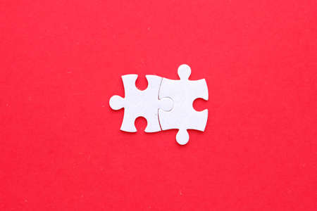 Two pieces of jigsaw puzzle connect on isolated red background.