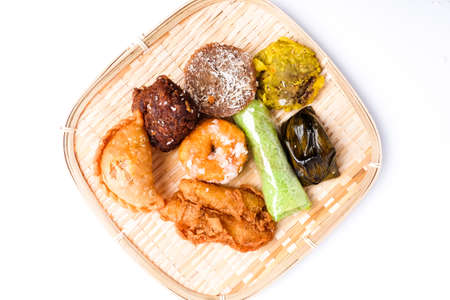 """A flatlay picture of famous Nusantara dessert or bitesized snack called """"kuih"""" on rattan plate. It is famous streets food in Malaysia and Indonesia."""