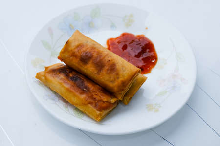 """Selective focus picture of """"popiah otak-otak"""" in the plate. Fish cake made of ground fish meat mixed with tapioca starch and spices in spring rolls."""