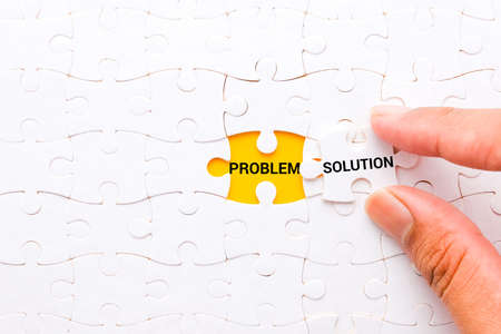 """A picture of hand try to put """"SOLUTION"""" jigsaw puzzle at """"PROBLEM"""" word on yellow background. Every problem have its solution. Standard-Bild"""