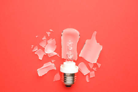 A picture of broken E27 type modelling light bulb on red background.
