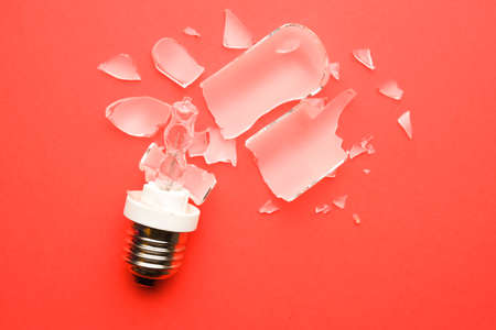 A picture of broken E27 type modelling light bulb on red background. Stockfoto