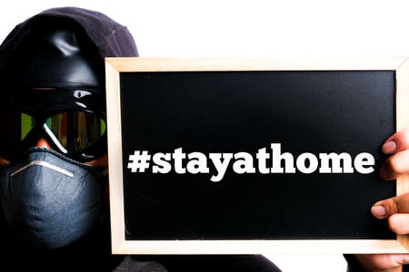A picture of men wearing N95 face mask, goggle and hood holding blackboard written #stayathome. During battling covid-19 many government impose movement restriction order and lockdown.