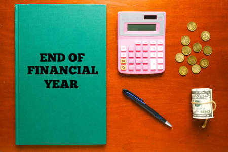Flatlay picture of green account manuscript book written End Of Financial Year with calculator, pen, fake cash and coin for