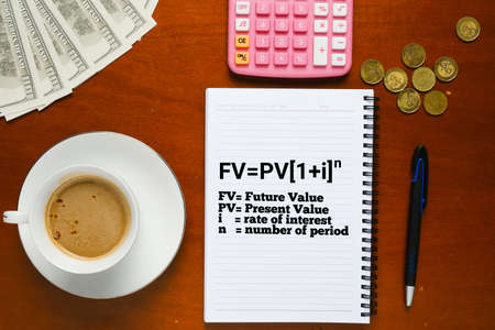 Flatlay picture of note book with end of future value formula, pen, milk coffee, fake cash, coins and calculator. Stock Photo