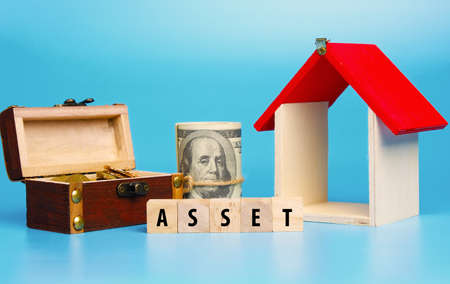 A picture of wooden block written ASSET, house miniature, gold chest and fake money.