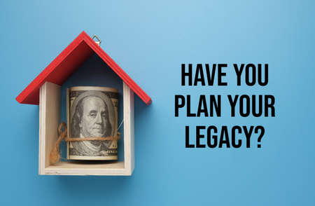 A picture of money with house miniature and word have you plan your legacy. Legacy planning is a financial strategy that prepares people to bequeath their assets to a loved one or next of kin after death.
