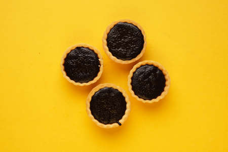 A picture of four homemade chocolate tart on yellow background. Same colour subject and background concept