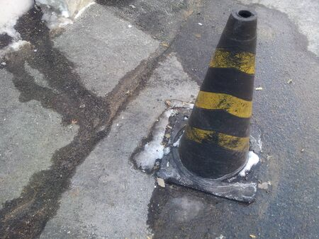 Traffic cone with yellow and grey strips on grey asphalt, Road construction warning cone