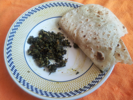 A close-up on a plate: Palak Saag with roti, a traditional Pakistani cuisine, served in a ceramic plate with bread Stock Photo