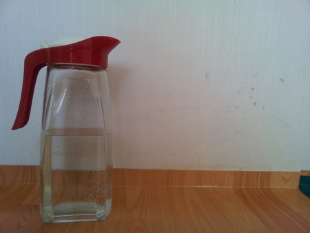 Glass water jug on wooden floor beside white wall background with copy space for text Stock Photo