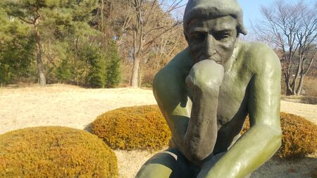 Green statue of thinker Auguste Rodin, setting naked on a rock in a public park 写真素材
