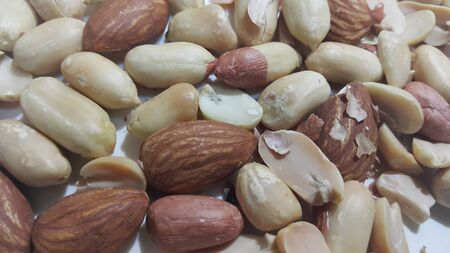 Closeup view of mixed dried and roasted  peanuts and almonds. A fruit for background text