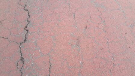 Red colored damaged road or paved pathway with crackes of different shpaes. Cracked texture with copy space for text and messages 写真素材