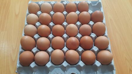 Fresh farm chicken eggs in an egg-carton or egg holder or paper tray placed in market for sale