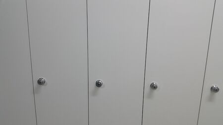 Perspective view of lockers or cupboards in a row with white doors, keys and locks