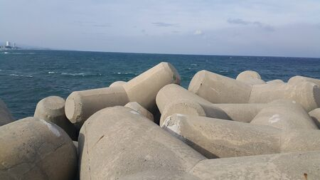 Close view of tetrapod stones on the sea shore to prevent coastal ersosion. Break water concrete tetrapods.