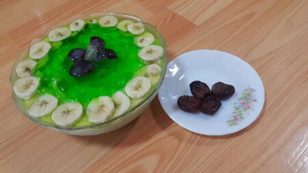 Creamy tasty sweet green jelly over custard with banana slices layered on surface on wooden floor. A top view of home made custard, a dairy products for dessert after meal. Imagens