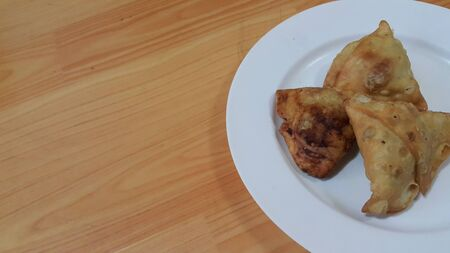 Closeup of delicious home made spicy and crunchy samosa pastries placed in a white ceramic plate on wooden floor