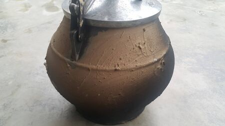 Pressure cooker covered with mud for cooking on fire. Cauldron type rural pressure cooker. 写真素材