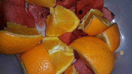 Closeup view of mixed fruits slices of oranges and red water melon served in a ceramic white plate. Water melon is sweet while oranges are citrus in taste