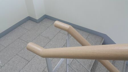 Closeup view of wooden handrail of grey concrete stairs in a modern building. Handrails help people avoiding accidents while moving on stairs. Stock Photo