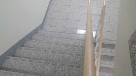 Closeup view of wooden handrail of grey concrete stairs in a modern building. Handrails help people avoiding accidents while moving on stairs.
