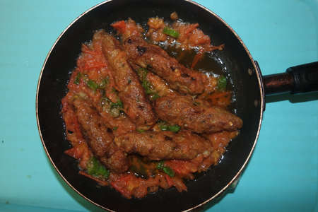 Closeup view of delicious spicy home made fried kebab with green mint leaves and green pepper sprinkled on it