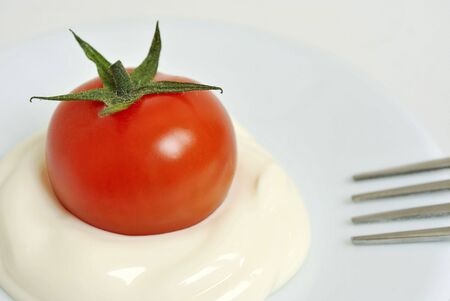 Red cherry tomato with mayonnaise on a saucer and a fork