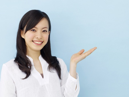 Young japanese girl isolated on blue background photo