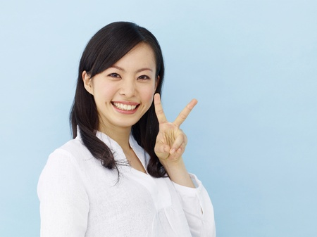 victory stand: Happy young japanese girl showing victory sign isolated on blue background Stock Photo