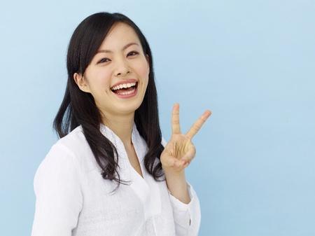 segno della pace: Felice giovane ragazza giapponese che mostra il segno della vittoria isolato su sfondo blu